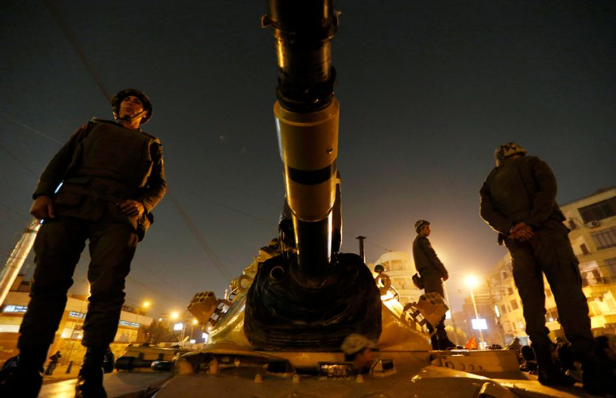Soldiers stand guard atop a tank in front of the presidential palace in Cairo on Dec. 9, 2012. (Associated Press)