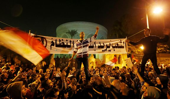 "Protesters chant slogans during a demonstration in front of the presidential palace in Cairo on Dec. 9, 2012.  The banner in the background reads, in Arabic, ""the people want to end the regime."" (Associated Press)"