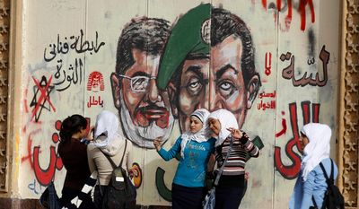 Young girls pose for a photograph by a wall painted with graffiti showing President Mohammed Morsi (left) and a split portrait of former Defense Minister Hussain Tantawi (center) and former President Hosni Mobarak in front of the presidential palace in Cairo on Dec. 10, 2012. (Associated Press)