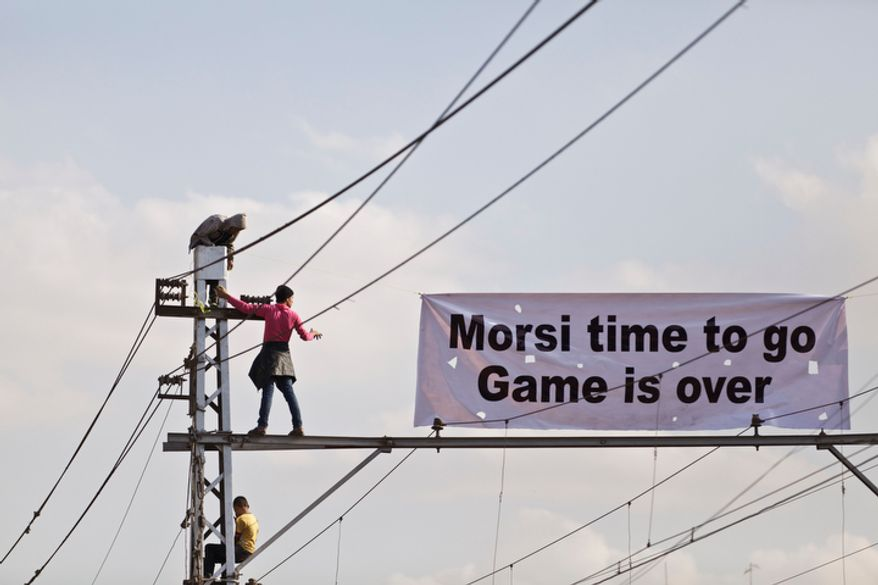 """Protesters opposed to Egyptian President Mohammed Morsi hang a banner outside the palace in Cairo on Dec. 8, 2012. Egypt's military said that serious dialogue is the """"best and only"""" way to overcome the nation's deepening conflict. (Associated Press)"""