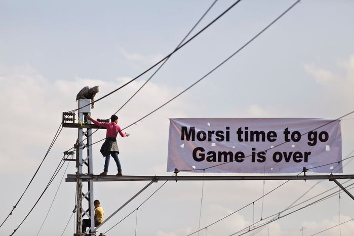 """Protesters opposed to Egyptian President Mohammed Morsi hang a banner outside the palace in Cairo, Egypt, Saturday, Dec. 8, 2012. Egypt's military said Saturday that serious dialogue is the """"best and only"""" way to overcome the nation's deepening conflict. (AP Photo/Maya Alleruzzo)"""