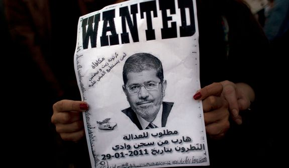 "An Egyptian protester carries a poster with a picture of President Mohammed Morsi and Arabic that reads ""wanted for justice, escaped from the Natroun valley prison in January 29, 2011, Reward, a box of oil and two eggs"" during an anti-Morsi protest near the presidential palace in Cairo on Dec. 7, 2012. (Associated Press)"