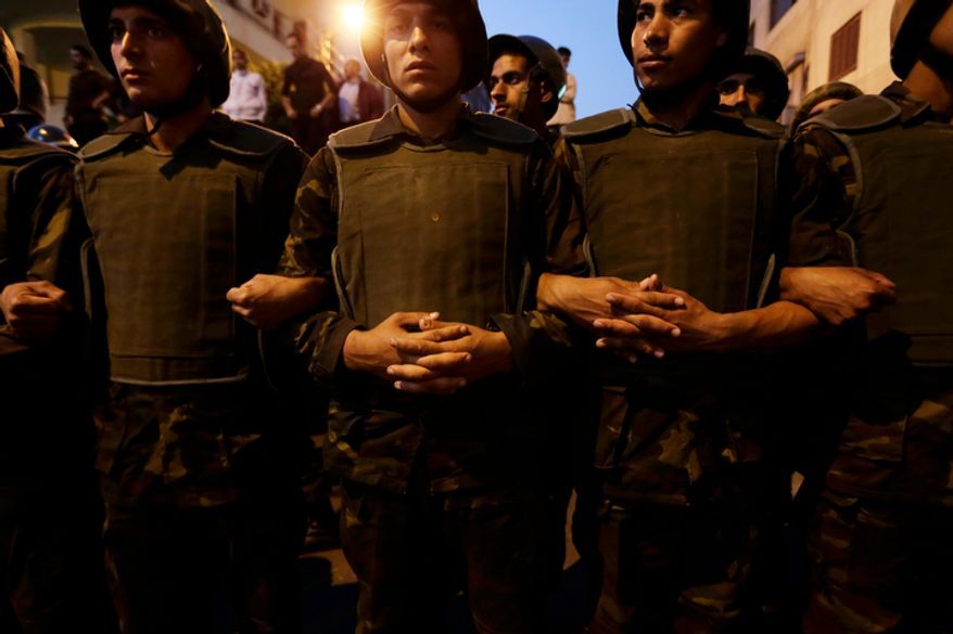 Egyptian army soldiers stand guard Dec. 9, 2012, near the presidential palace in Cairo. Egypt's liberal opposition called for more protests, seeking to keep up the momentum of its street campaign after the president made a partial concession overnight but refused its main demand he rescind a draft constitution going to a referendum on Dec. 15. (Associated Press)