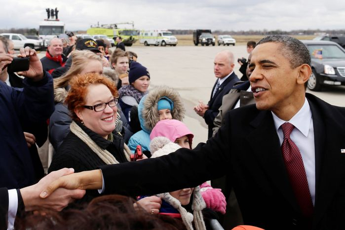 President Obama greets well-wishers after stepping off Air Force One upon his arrival at the Detroit Metropolitan Wayne County Airport in Romulus, Mich., on Monday, Dec. 10, 2012, before going to the Daimler Detroit Diesel plant in Redford. (AP Photo/Charles Dharapak)