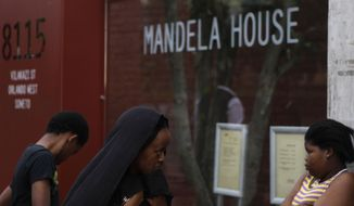 People visit former South African President Nelson Mandela's home, which has been turned into a museum, in Soweto, South Africa, on Sunday, Dec. 9, 2012. (AP Photo/Denis Farrell)