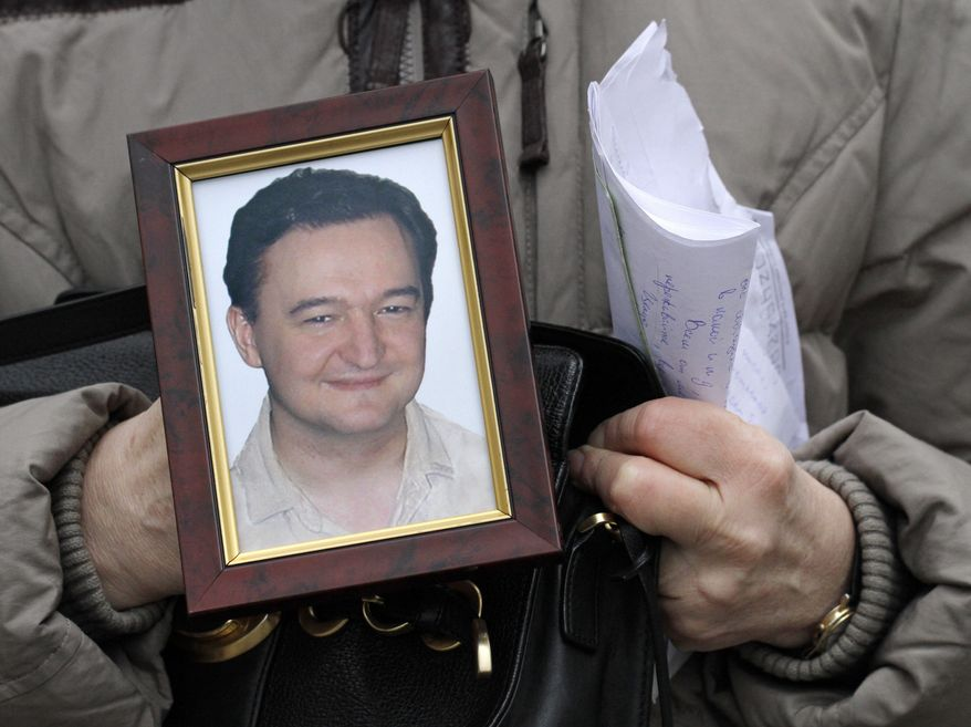 Nataliya Magnitskaya, mother of Russian lawyer Sergei Magnitsky, who died in jail, holds his portrait during an interview with the AP in Moscow in 2009. (AP Photo/Alexander Zemlianichenko)