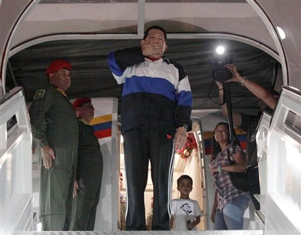 Venezuelan President Hugo Chavez (center) blows a goodbye kiss prior to boarding his plane at the Simon Bolivar International airport in Maiquetia near Caracas, Venezuela, on Dec 10, 2012. (Associated Press/Miraflores Press Office)