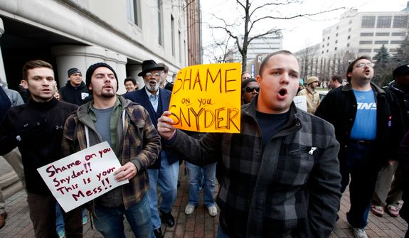 Demonstrators protest right-to-work legislation in the outside the George W. Romney State Office building, where Gov. Snyder's office is located, in Lansing, Mich., Friday, Dec. 7, 2012. Michigan could become the 24th state with a right-to-work law next week. Rules require a five-day wait before the House and Senate vote on each other's bills; lawmakers are scheduled to reconvene Tuesday and Gov. Snyder has pledged to sign the bills into law. (AP Photo/Paul Sancya)