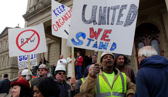 Union workers rally outside the Capitol in Lansing, Mich., Thursday, Dec. 6, 2012 as Senate Republicans introduced right-to-work legislation in the waning days of the legislative session. The outnumbered Democrats pledged to resist the proposal and said rushing it through the legislative system would poison the state's political atmosphere. (AP Photo/Carlos Osorio)
