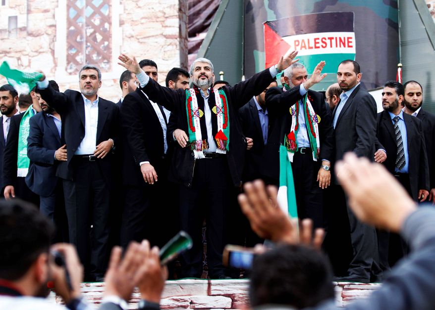 Exiled leader Khaled Mashaal (center), in his first visit to Gaza, joins Hamas Prime Minister Ismail Haniyeh (right) to celebrate the 25th anniversary of the militant group. Once the target of an Israeli assassination attempt, Mr. Mashaal now is confident enough to enter Gaza and walk around in public. (Associated Press)