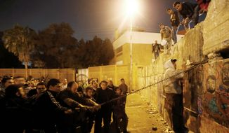 Protesters dismantle a wall guarding the presidential palace during a demonstration against President Mohammed Morsi in Cairo on Tuesday. Offices of Mr. Morsi's Muslim Brotherhood political party were also targeted. Backers of the president also turned out for demonstrations to show their support. (Associated Press)