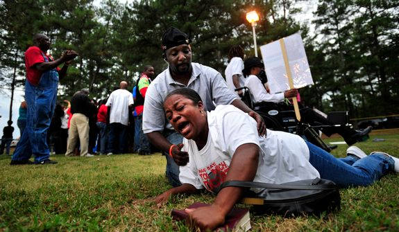 **FILE** An anti-death penalty protester in Jackson, Ga., is helped off the ground Sept. 21, 2011, after hearing about a delay of the execution of Georgia death row inmate Troy Davis by the U.S. Supreme Court. Davis was convicted of killing off-duty Savannah officer Mark MacPhail. (Associated Press)