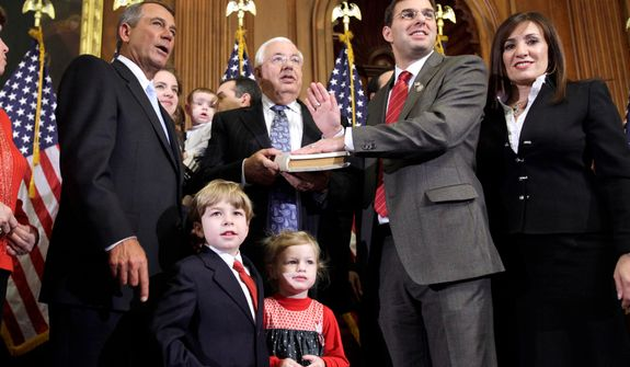 House Speaker John A. Boehner (left), Ohio Republican, administers the House oath to Rep. Justin Amash, Michigan Republican, during a mock swearing-in ceremony on Capitol Hill in Washington on Wednesday, Jan. 5, 2011. (AP Photo/Jacquelyn Martin)