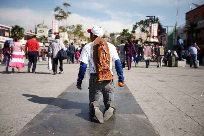 A pilgrim walks on his knees carrying an image of the Virgin of Guadalupe on his back as he makes his way to the Basilica of Guadalupe in Mexico City, Tuesday Dec. 11, 2012. Nationwide, devotees of the Virgin of Guadalupe make a pilgrimage to the basilica in honor of her Dec. 12 feast day. (AP Photo/Denisse Pohls)