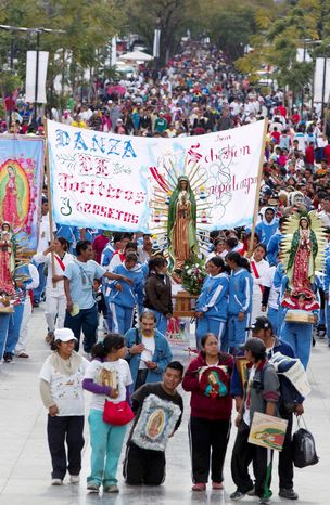 Pilgrims carry images of the Virgin of Guadalupe as they arrive to the Basilica of Guadalupe in Mexico City, Tuesday, Dec. 11, 2012.  (AP Photo/Eduardo Verdugo)