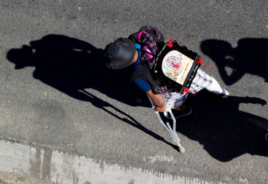 A man using crutches carries an image of the Virgin of Guadalupe on his back as he walks along a highway entering the capital during his pilgrimage to the Basilica of Guadalupe, Tuesday Dec. 11. 2012. Nationwide, devotees of the Virgin of Guadalupe make a pilgrimage to the Basilica in honor of her Dec. 12 feast day. (AP Photo/Eduardo Verdugo)