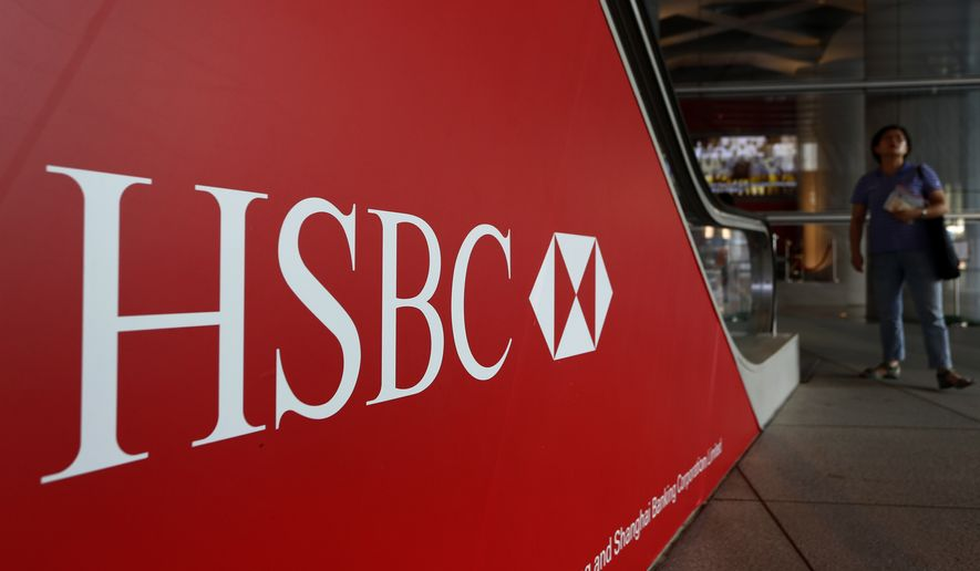 In this file photo, pedestrians pass a sign with the HSBC logo in Hong Kong on Monday, July 30, 2012.  On Jan. 18, 2018, the U.S. Department of Justice announced that HSBC Holdings has agreed to pay $101.5 million to settle claims it defrauded two of its clients. (AP Photo/Vincent Yu)