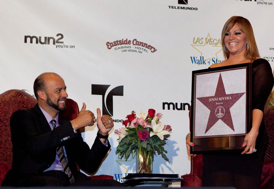 **FILE** Singer Jenni Rivera (right) poses with a replica of a star for the Las Vegas Walk of Stars as her husband, former Major League Baseball pitcher Esteban Loaiza, reacts during an official presentation ceremony in Las Vegas on July 1, 2011. (Associated Press)