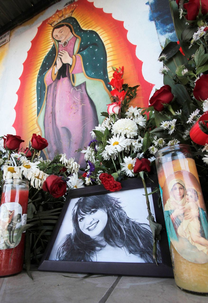 Photos and flowers honoring late singer Jenni Rivera, placed by fans next to religious images, are seen at the cemetery where her mother is buried in Hermosillo, Mexico, on Dec. 10, 2012. (Associated Press)