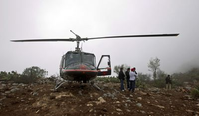 A rescue helicopter with members of the Mexican General Civil Aeronautic Directorate stand Dec. 10, 2012, atop a hill next to the canyon where U.S.-born singer Jenni Rivera's jet crashed near the town of Iturbude, Mexico, the previous day. (Associated Press)