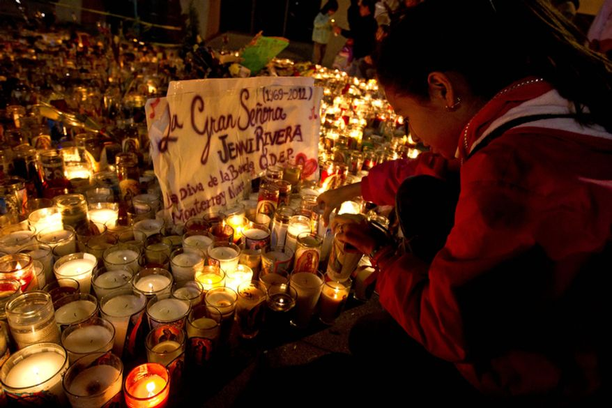 A fan of Jenny Rivera lights a candle at the Basilica of Guadalupe in Monterrey, Mexico, on Dec. 10, 2012. (Associated Press)
