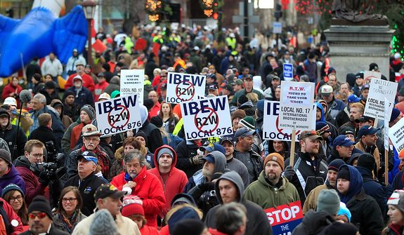 Thousands of protesters gather for a rally on the state Capitol grounds in Lansing, Mich., on Tuesday, Dec. 11, 2012. The crowd is protesting legislation that would make Michigan the 24th right-to-work state, banning requirements that nonunion employees pay unions for negotiating contracts and other services. (AP Photo/Carlos Osorio)