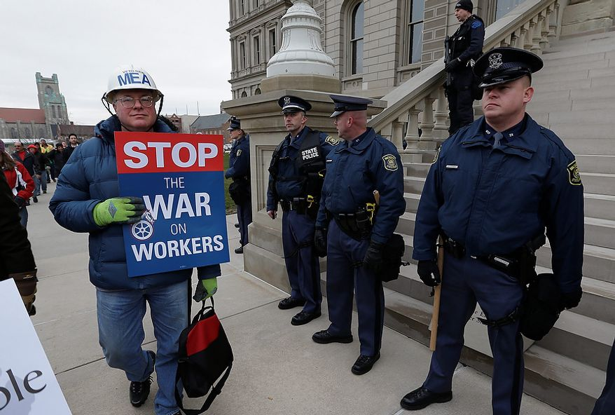 A protester walks past Michigan State Police officers at the Capitol in Lansing, Mich., on Tuesday, Dec. 11, 2012. Demonstrators are protesting legislation that would make Michigan the 24th state with a right-to-work law. (AP Photo/Paul Sancya)