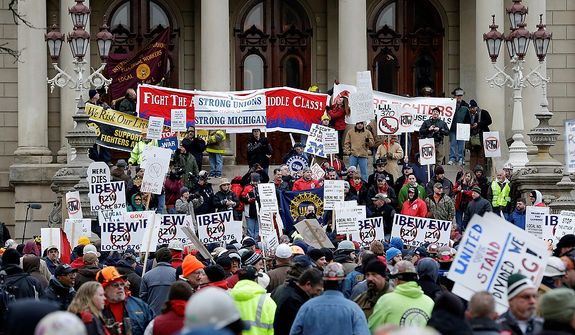 Protesters gather for a rally on the state Capitol steps in Lansing, Mich., on Tuesday, Dec. 11, 2012. The crowd is demonstrating against legislation that would make Michigan the 24th state with a right-to-work law. (AP Photo/Paul Sancya)