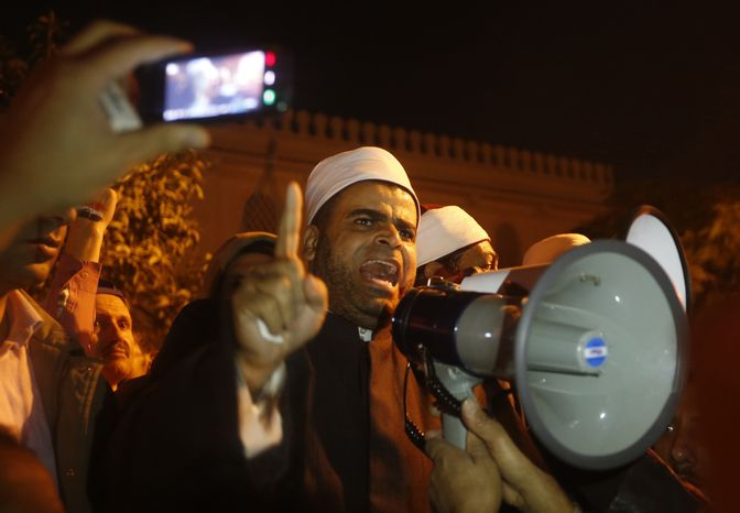 A cleric from Al-Azhar, Egypt's most respected Islamic institution, addresses protesters in front of the presidential palace during a demonstration in Cairo on Dec. 11, 2012. Thousands of opponents and supporters of Egypt's Islamist president staged rival rallies in the nation's capital, four days ahead a nationwide referendum on a contentious draft constitution. (Associated Press)