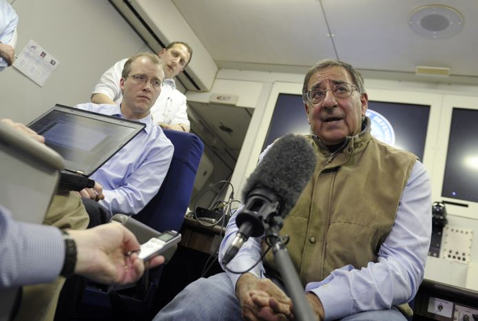 Defense Secretary Leon E. Panetta (right) talks to reporters on board his plane while headed to Kuwait on Monday, Dec. 10, 2012. Mr. Panetta will meet with U.S. troops as part of a visit to thank them for their service. (AP Photo/Susan Walsh, Pool)