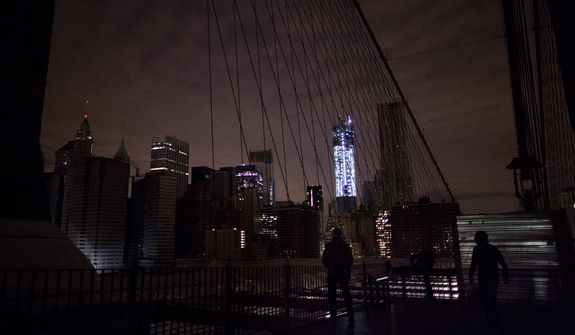 Much of lower Manhattan remains dark, as viewed from the darkened Manhattan side of the pedestrian walkway of the Brooklyn Bridge in New York, on Thursday, Nov. 1, 2012. Power outages plagued much of the New York area in the wake of superstorm Sandy. (AP Photo/Craig Ruttle)