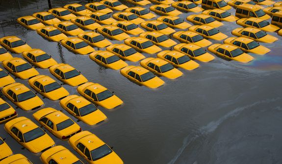 A parking lot full of yellow cabs is flooded as a result of superstorm Sandy in Hoboken, N.J., on Tuesday, Oct. 30, 2012. (AP Photo/Charles Sykes)