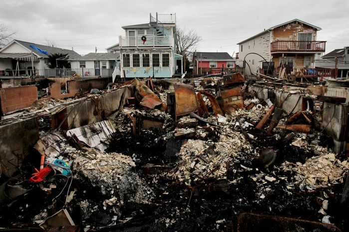 ** FILE ** A Christmas wreath is displayed on the second-floor porch railing of a home adjacent to the fire-damaged zone in the Breezy Point section of the New York borough of Queens on Friday, Dec. 7, 2012. More than 100 homes burned to the ground during Superstorm Sandy. (AP Photo/Mark Lennihan)