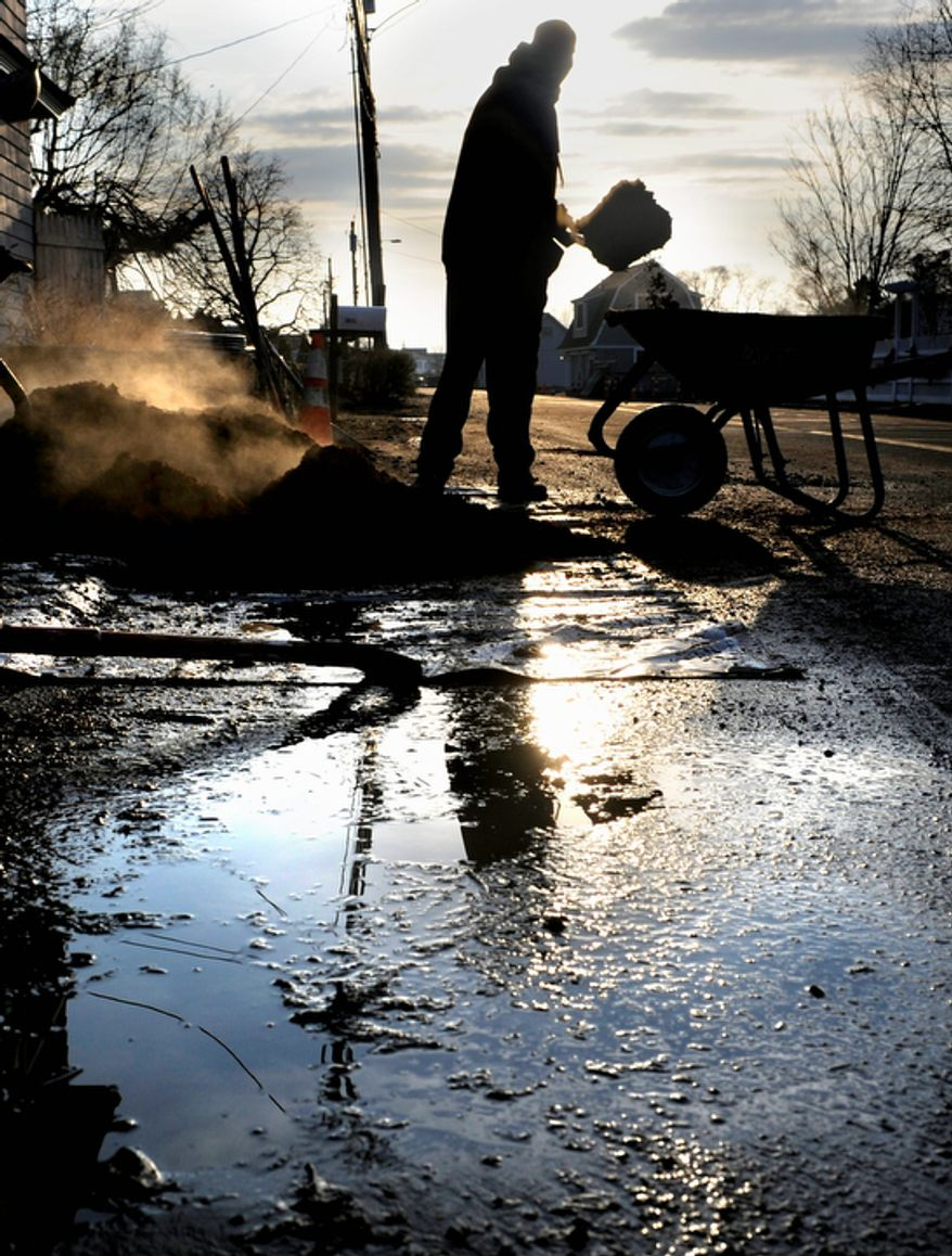 A landscaper loads mulch into a wheelbarrow at a beachfront home in Fairfield, Conn., on Tuesday, Dec. 4, 2012. The national economy is expected to absorb the blow from superstorm Sandy with little long-term damage, but in the short term, at least, Sandy is introducing dramatic booms and busts across the Northeast. (AP Photo/Jessica Hill)