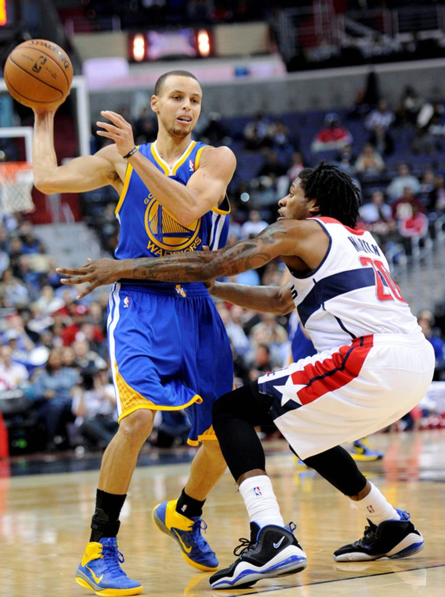 Golden State Warriors guard Stephen Curry (left) tries to get around Washington Wizards forward Cartier Martin during the first half of the Warriors' 101-97 win on Dec. 8, 2012, in Washington. (Associated Press)