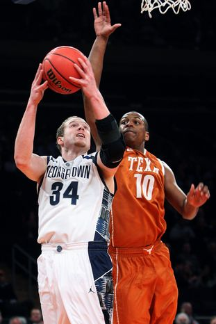 Georgetown's Nate Lubick (34) drives past Texas' Jonathan Holmes (10) during the first half of their NCAA college basketball game in the Jimmy V Classic, Tuesday, Dec. 4, 2012, at Madison Square Garden in New York. (AP Photo/Frank Franklin II)