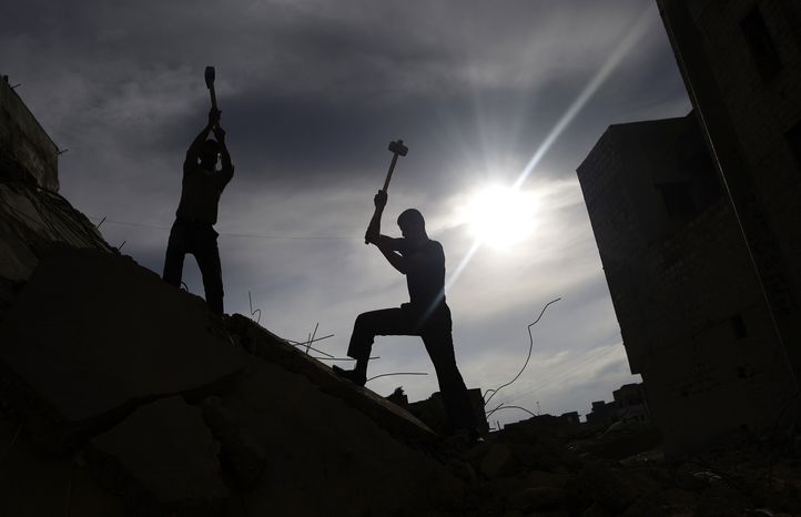 Syrian men use sledgehammers to break the concrete of a residential building in Maaret Misreen, near Idlib, Syria, on Dec. 12, 2012, while searching for belongings under the rubble. The building was destroyed in a government airstrike. (Associated Press)