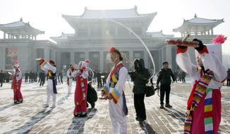North Korean youths in traditional Korean outfit play instruments in front of the Pyongyang Grand Theatre in Pyongyang, North Korea, on Dec. 12, 2012, to celebrate a rocket launch. North Korea appeared to successfully fire a long-range rocket, defying international warnings as the regime of Kim Jong Un pushes forward with its quest to develop the technology needed to deliver a nuclear warhead. (Associated Press)
