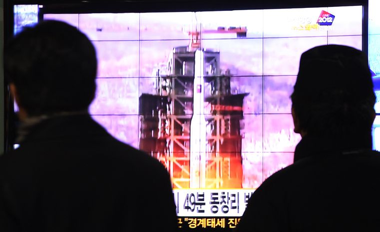 South Koreans at Seoul Station in the nation's capital watch a TV news report on the launch of an Unha rocket from Tongchang-ri, North Korea, on Wednesday, Dec. 12, 2012. The launch by North Korea of the long-range rocket came only days before South Korean presidential elections. (AP Photo/Ahn Young-joon)