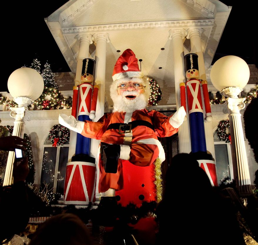A giant Santa Claus stands amid other Christmas decorations outside a home in Brookyn, where neighbors dress up their yards and home exteriors in grand style. (Associated Press)