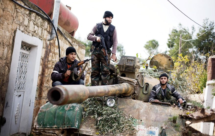 Kurdish members of the Free Syria Army ride on a tank stolen from the Syrian army in Fafeen village, north of Aleppo, in Syria on Wednesday. The rebels have made significant gains on the ground in Damascus, Deir al-Zour and Aleppo, where they have overrun military bases. (Associated Press)