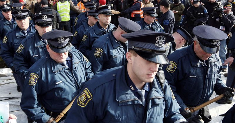 Michigan State Police officers march out of the area where the Americans for Prosperity tent was taken down by protesters Tuesday. Many protesting a right-to-work bill took out their anger out with the group, which supported the legislation. Some people were trapped inside, and others said they were threatened. (Associated Press)
