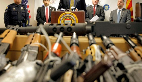 """Bill Newell, special agent in charge of ATF Phoenix, speaks Jan. 25, 2011, behind a cache of seized weapons in Phoenix. The ATF is under fire over a Phoenix-based gun-trafficking investigation called """"Fast and Furious,"""" in which agents allowed hundreds of guns into the hands of straw purchasers in hopes of making a bigger case. (Associated Press) **FILE**"""