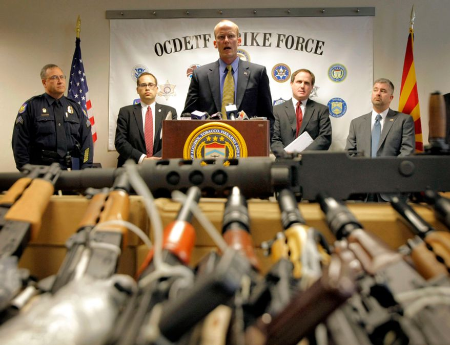 "Bill Newell, special agent in charge of ATF Phoenix, speaks Jan. 25, 2011, behind a cache of seized weapons in Phoenix. The ATF is under fire over a Phoenix-based gun-trafficking investigation called ""Fast and Furious,"" in which agents allowed hundreds of guns into the hands of straw purchasers in hopes of making a bigger case. (Associated Press) **FILE**"