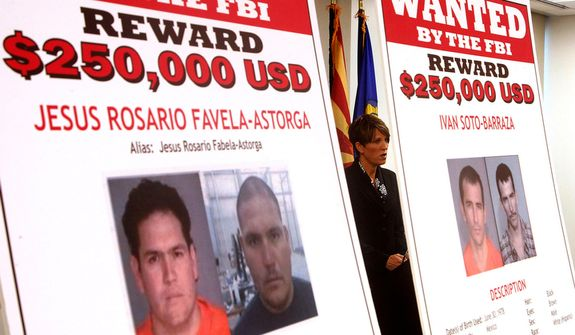 **FILE** Laura E. Duffy, United States Attorney Southern District of California, is flanked by wanted posters as she announces the indictment of five suspects related to the death of U.S. Border Patrol Agent Brian Terry during a news briefing in Tucson, Ariz., on July 9, 2012. (Associated Press)