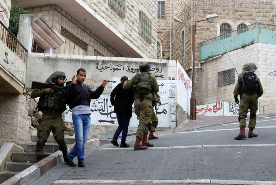 Israeli soldiers detain Palestinian youths during the funeral Mohammed Suleima, 17, in the West Bank city of Hebron, Thursday, Dec. 13, 2012. (AP Photo/Nasser Shiyoukhi)
