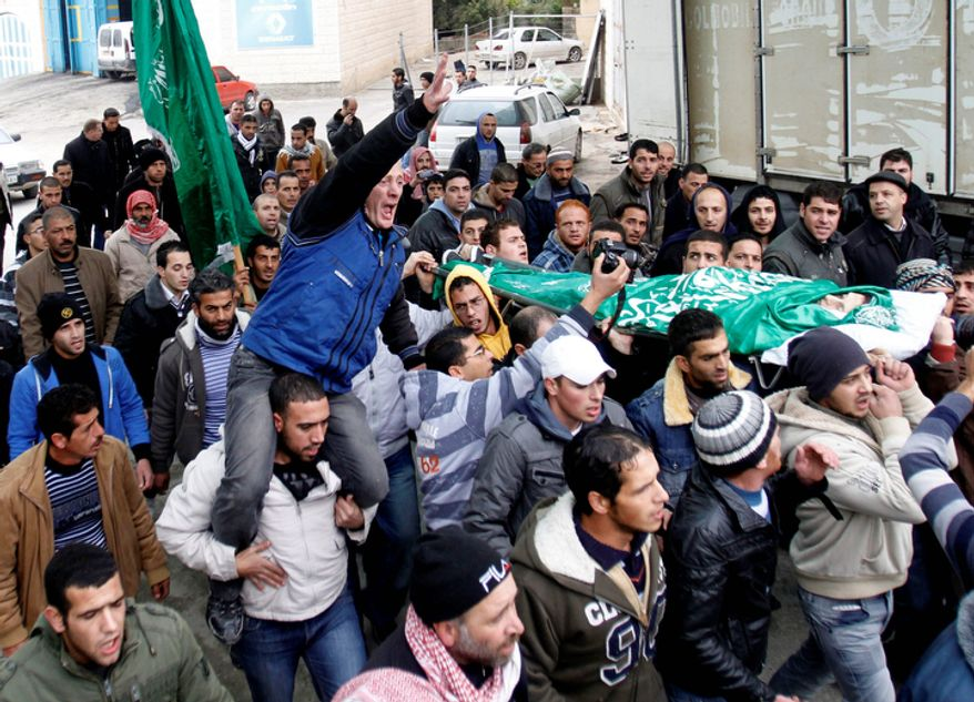 Palestinians carry the body of Mohammed Suleima, 17, during his funeral in the West Bank city of Hebron, Thursday, Dec. 13, 2012. (AP Photo/Nasser Shiyoukhi)