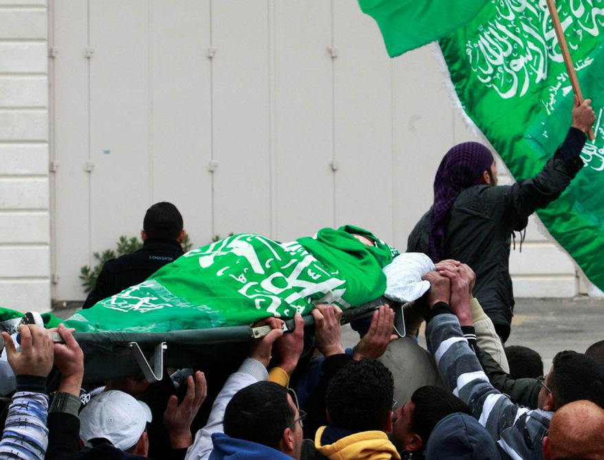Palestinians carry the body of Mohammed Suleima, 17, during his funeral in the West Bank city of Hebron, Thursday, Dec. 13, 2012. Thousands of Palestinians marched through the streets of this West Bank city on Thursday, chanting anti-Israel slogans and waving green Hamas flags during a funeral procession for a teenager killed by Israeli troops. (AP Photo/Nasser Shiyoukhi)