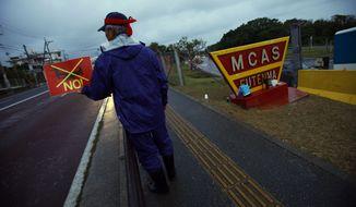 A protester flashes an anti-Osprey placard at a gate of the U.S. Marine Corps Air Station Futenma in Ginowan, Okinawa, in southwestern Japan, on Friday, Nov. 30, 2012. (AP Photo/Junji Kurokawa)