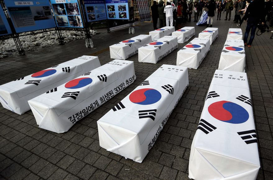South Korean protesters and former North Korean defectors display mock coffins symbolizing victims killed during the era of North Korea's late Kim Jong Il during a rally in Seoul on Dec. 13, 2012, denouncing North Korea's rocket launch. (Associated Press)